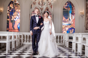 Portrait of confident wedding couple standing arm in arm at churchの写真素材 [FYI03658201]