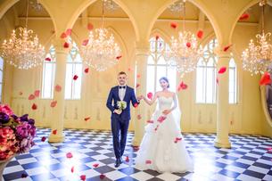 Full length of elegant wedding couple holding hands in churchの写真素材 [FYI03658207]