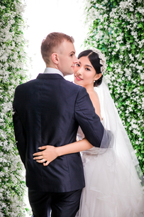 Portrait of smiling bride standing with bridegroom against flower decorationsの写真素材 [FYI03658216]