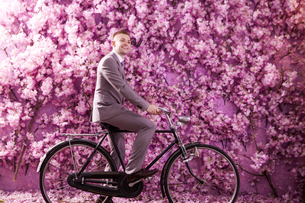 Side view of smiling bridegroom riding bicycle against wall covered with pink flowersの写真素材 [FYI03658222]