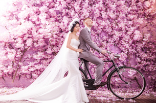 Thoughtful bride standing with bridegroom riding bicycle against pink flowers covering wallの写真素材 [FYI03658223]