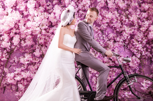 Wedding couple looking at each other against wall covered with pink flowersの写真素材 [FYI03658225]