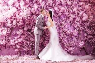 Side view of wedding couple kissing white standing against wall covered with pink flowersの写真素材 [FYI03658226]