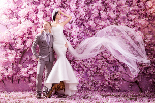 Full length of wedding couple standing against wall covered with pink flowersの写真素材 [FYI03658227]