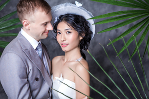 Portrait of beautiful bride standing with bridegroom against wallの写真素材 [FYI03658228]