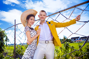 Portrait of happy couple standing by fence at field against skyの写真素材 [FYI03658230]