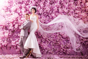 Portrait of confident wedding couple standing against wall covered with pink flowersの写真素材 [FYI03658232]