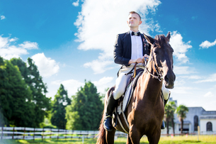 Thoughtful well-dressed man sitting on horse against cloudy skyの写真素材 [FYI03658241]
