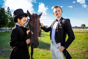 Portrait of confident man standing with horse and woman on fieldの写真素材 [FYI03658249]
