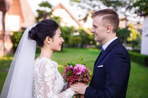 Side view of smiling wedding couple holding bouquet at lawnの写真素材 [FYI03658255]