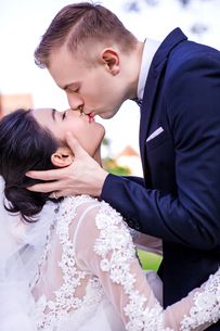 Side view of romantic wedding couple kissing against skyの写真素材 [FYI03658257]