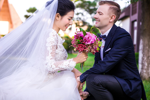 Happy bridegroom looking at beautiful bride holding bouquet outdoorsの写真素材 [FYI03658258]
