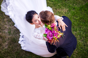 High angle view of romantic wedding couple on grassy fieldの写真素材 [FYI03658259]