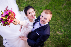 High angle portrait of cheerful wedding couple standing on grassy fieldの写真素材 [FYI03658261]