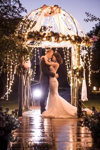 Side view of elegant couple embracing in illuminated gazebo at nightの写真素材 [FYI03658269]