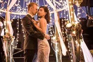 Romantic couple embracing in illuminated gazebo at nightの写真素材 [FYI03658274]
