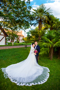 Portrait of wedding couple standing at lawnの写真素材 [FYI03658279]
