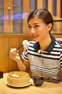 Chinese Woman eating Steamed dumpling in restaurantの写真素材 [FYI03658281]