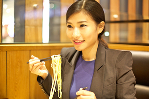 Chinese Woman eating noodles in restaurantの写真素材 [FYI03658282]