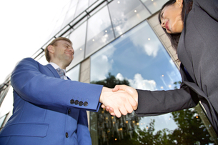 Low angle view of Multi ethnic business couple shaking handsの写真素材 [FYI03658287]
