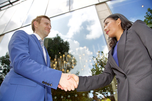 Low angle view of Multi ethnic business couple shaking handsの写真素材 [FYI03658292]