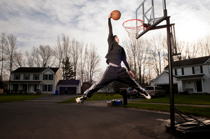 Portrait of teen (14-15 ) dunking on netの写真素材 [FYI03659145]