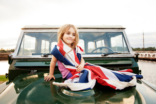 Girl (2-3) wrapped up in British flag sitting on car hoodの写真素材 [FYI03659304]