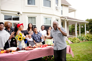 Man dancing outdoors at family reunion,  in front of family with childrenの写真素材 [FYI03660634]
