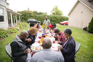 Family members with children praying before meal at family reunionの写真素材 [FYI03660637]