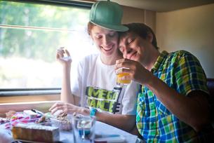 Young couple enjoying snack on trainの写真素材 [FYI03660867]