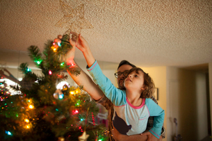 Father and daughter (8-9) putting tree topper on Christmas treeの写真素材 [FYI03661986]