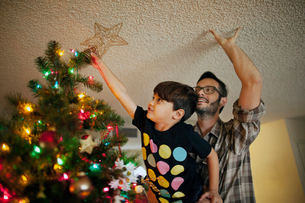 Father and son (6-7) putting tree topper on Christmas treeの写真素材 [FYI03661990]