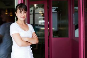 Portrait of waitress standing in front of restaurantの写真素材 [FYI03662089]