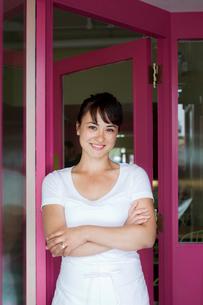 Portrait of waitress standing in front of restaurantの写真素材 [FYI03662090]