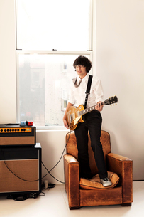 Portrait of young man on armchair with guitarの写真素材 [FYI03662623]