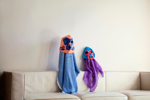 Siblings sitting on sofa dressed as fictional characters,の写真素材 [FYI03662760]