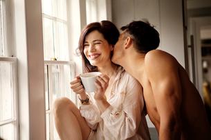 Man kissing teasing woman over coffeeの写真素材 [FYI03663025]