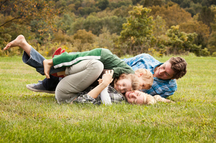 Family wrestling with children (2-3) (6-7) on grassの写真素材 [FYI03663296]