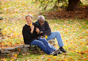 Senior couple sitting side by side on curb of flower bed laughingの写真素材 [FYI03663381]