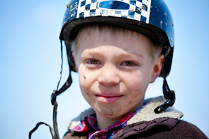 Young boy(8-9) with helmet on and dirty faceの写真素材 [FYI03663488]