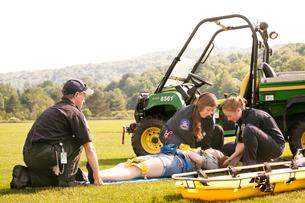 Emergency medical technicians lifting woman to gurneyの写真素材 [FYI03663613]