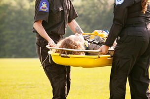Emergency medical technicians carrying woman on gurneyの写真素材 [FYI03663615]