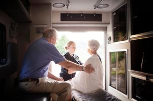 Emergency medical technician assisting elderly couple in ambulanceの写真素材 [FYI03663634]