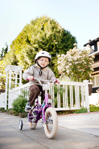 Girl (4-5) riding bicycle with training wheelsの写真素材 [FYI03665612]
