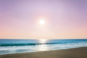 浜辺に寄せる波と朝日の写真素材 [FYI03666922]