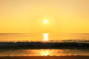 浜辺に寄せる波と朝日の写真素材 [FYI03666926]