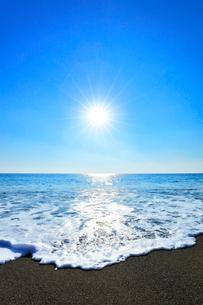 浜辺に寄せる波と朝日の写真素材 [FYI03666964]