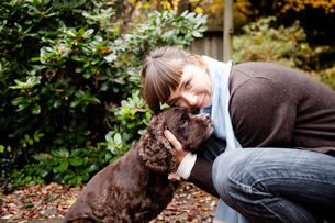 Young woman loving her spaniel in autumnの写真素材 [FYI03667038]