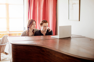 Couple playing piano with help from laptopの写真素材 [FYI03667181]