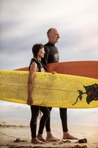 Senior surfers standing on beach and holding surfboardの写真素材 [FYI03668442]
